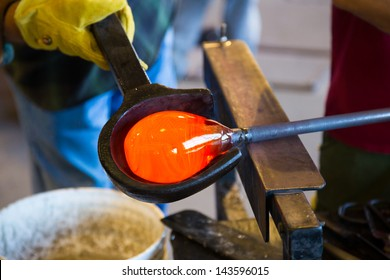 A very talented glassblower is forming and shaping glass in a studio for glass making. He is creating a fluted bowl from this piece of molten glass.
