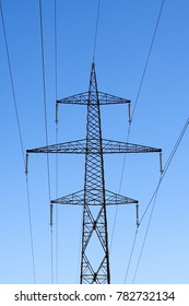 A very tall high voltage electricity line sustained by a big metal pole with lots of wires attached