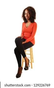 A very tall young teenage girl sitting on a chair in a orange sweater and black tights and heels for white background.