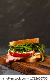 Very tasty big sandwich with ham or balyk, arugula, cheese, tomatoes and mayonnaise on a cutting board in rustic style on a gray background view from the side, copy space