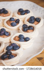A very tender delicious pastry custard nest with blueberries on a white dish. Fresh organic meringues for the holiday.