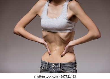 Very thin girl shows her skinny waist, covering his hands. Image is a close-up