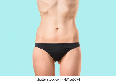 Very thin young woman with protruding bones and ribs suffering from extreme dieting, starvation or an eating disorder such as bulimia or anorexia isolated on white, close up torso shot
