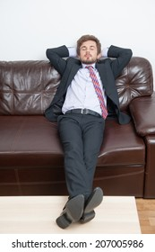Very tired businessman having a rest in his office after hard working day and dreaming about warm soft bed at home