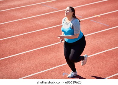 Very tired fat young woman having cardio training in hot weather on stadium
