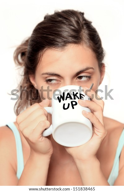 """very tired looking woman early in the morning drinking a cup of coffee to """"wake up"""" - selective focus on cup - isolated on white"""