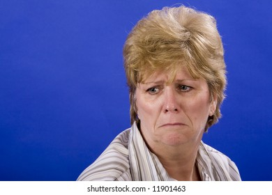 very unhappy woman on blue back ground