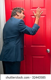 Very upset businessman knocking off a door trying to collect a debt.