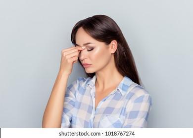 Very upset, charming, nice woman touching nose between closed eyes over grey background, want to cry, having stressful relationship, worry about conflict with her lover, having troubles with work