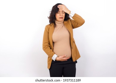 A very upset and lonely Young pregnant businesswoman wearing beige blazer over white background crying,