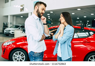 I very want exactly this red car! Young lovely couple in casual wear buying first car together in dealership.