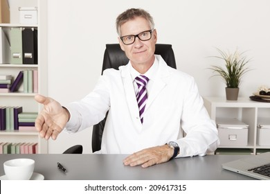very welcoming family doctor showing take a seat please hand sign, looking at camera