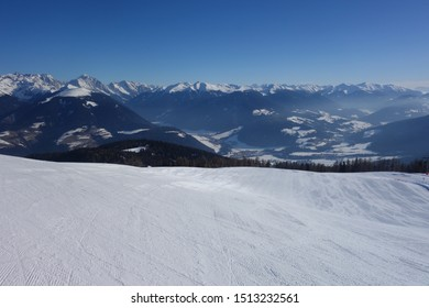 Very wide and completely empty skiing slope on a clear winter morning in Italy (Kronplatz) with blue skies and mountain peaks in the distance