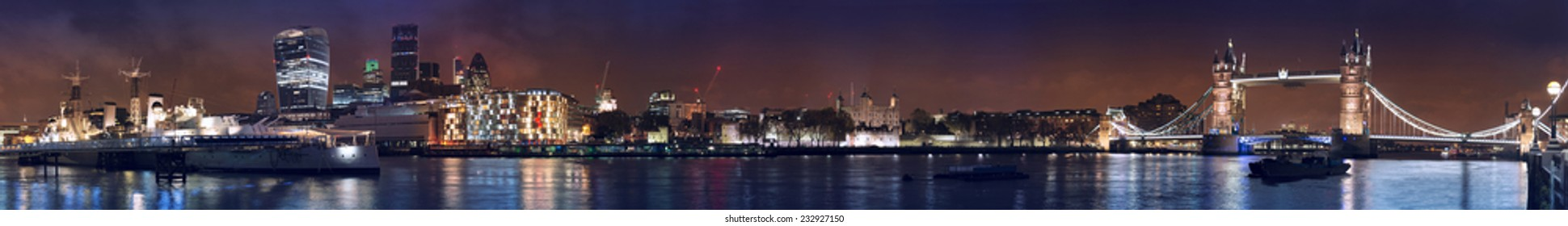 Very wide night panorama of London Tower bridge, Tower, financial City district and HMS Belfast warship museum.