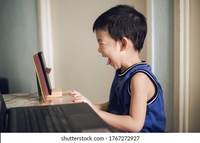 Very young, 5 year old Asian boy smiling happily and sticking out toungue while learning in online class using mobile device during Covid19 at home.