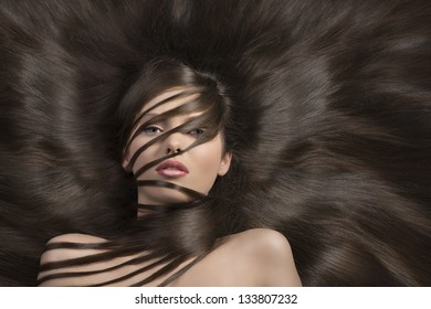 very young and cute girl with long and creative hairstyle  laying down and some locks on the face and the neck