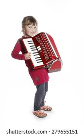 very young girl with accordion in studio against white background