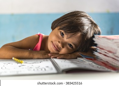 a very young girl student in the school has her head on the exercise book and smiling friendly. Thai school in a small village