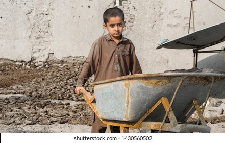 a very young orphan child is forced into child labor and working at a construction site and his expressions area full of pain