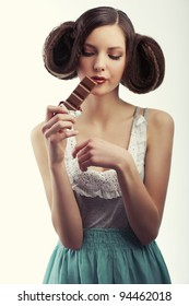very young pretty girl with creative hairstyle melting a tablet of chocolate wearing a old style dress