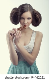 very young pretty vintage girl with creative hairstyle eating a tablet of chocolate wearing a old style dress