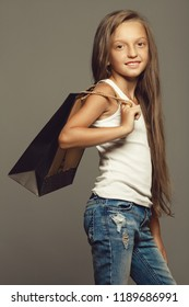 Very young shopaholic, great discounts concept. Portrait of a smiling little girl in casual clothing posing with eco paper package over gray background. Studio shop