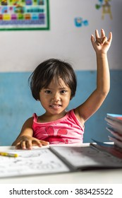 a very young student girl has a question for the teacher. Thai school in a small village