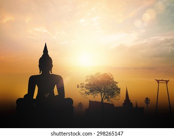 Vesak day concept: Silhouette Buddha with blurred tourist attraction in thailand on golden sunset background.