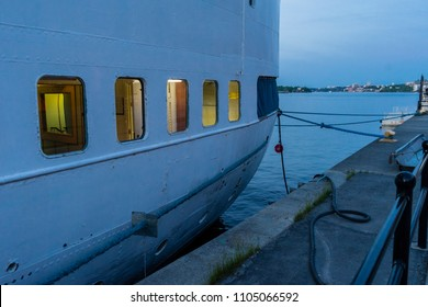 Vessel window lights/Late evening image on the quay of Sodermalm quarter in Stockholm with a cruiser ship docked to the shore with artificial lights on inside.