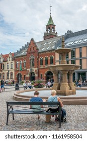 Vest-Agder, Norway -august 08, 2018: People sitting and walking around the fountain of Town Hall Square in the city of Kristiansand
