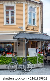 Vest-Agder, Norway -august 08, 2018: Bicycle and terrace of a restaurant in a corner of the main avenue of the city of Kristiansand, at sunset