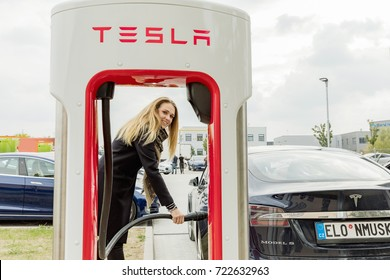 VESTEC, CZECH REPUBLIC - SEPTEMBER 23, 2017. Young woman joins a car to the Supercharger Tesla station. Supercharger charging station for electromobiles. Tesla cars park at the Tesla Supercharger.