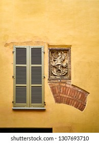 Vestiges of a Medieval Arch and a Blazon on a facade. Asti, Piedmont, Italy.