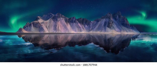 Vestrahorn mountaine on Stokksnes cape with Green northern lights and reflections. Amazing Iceland nature seascape.  Iconic location for landscape photographers and bloggers. Scenic Image of Iceland