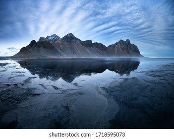 Vestrahorn mountains and Stokksnes beach near Hofn, southern Iceland. Mirror reflection and black vocanic sands at low tide.