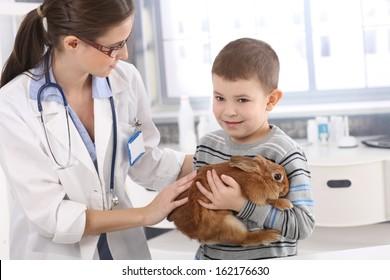 Vet helping little kid holding cute pet rabbit at pets' clinic.