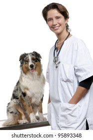 Vet standing next to an Australian Shepherd in front of white background