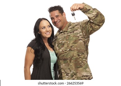 VETERAN SOLDIER and his military spouse buying a new car.  Sergeant and his wife or girlfriend with new car key on white background.  Military Lending | Payday Loan
