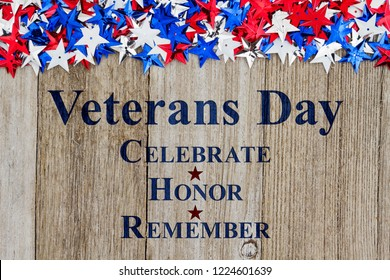 Veterans Day Celebrate Honor Remember text with red, white and blue stars on weather wood