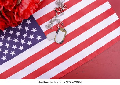 Veterans Day USA flag with dog tags and red flanders poppies on rustic red wood background, overhead with copy space.