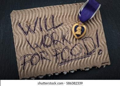 """Veterans reintegration and social issues concept with cardboard sign reading """"will work for food"""" and a purple heart medal illustrating the reality of many veterans that struggle to join civilian life"""