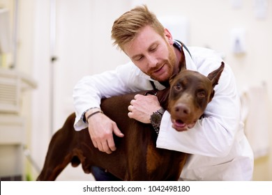 Veterinarian giving a hug to his patient, friedship between dog and man