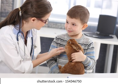 Veterinary and cute kid discussing rabbit treatment at pets' clinic.