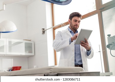Veterinary doctor using digital tablet while standing at clinic