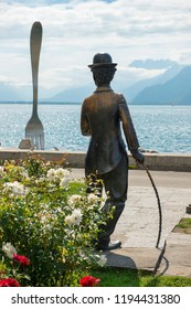 VEVEY, Switzerland - September 02: monument to Charlie Chaplin on the promenade in Vevey (Vaud) on the background giant fork sticking out of a Geneva lake, Switzerland on September 02, 2018
