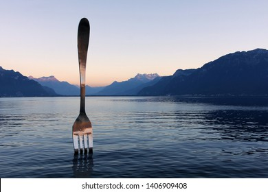 VEVEY, SWITZERLAND - September 30, 2016: Sunset scene of Lake Geneva (Leman) in Vevey, featuring The Fork, a work of art by Jean-Pierre Zaugg. It helds the world record as the biggest fork.