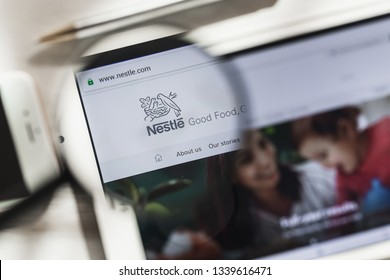 Vevey, Vaud, Switzerland - March 16, 2019: Nestle, S.A. official website homepage under magnifying glass. Concept Nestle, Retail logo visible on smartphone, tablet screen