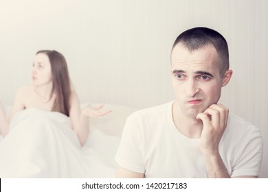 A vexed man and a woman in the bedroom, a girlfriend in the background, a frustrated man sitting on the bed, toned, the concept of problems in sex