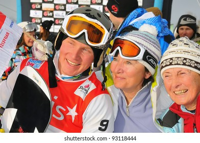VEYSONNAZ, SWITZERLAND - JANUARY 19: The 2012 FIS World Snowboard Cross Champion A Boldykov (L) of Russia poses for a photo with Russian fans at the snowboard cross finals on January 19, 2012 in Veysonnaz, Switzerland
