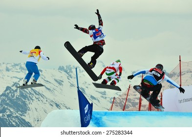 VEYSONNAZ, SWITZERLAND - MARCH 14: Finalists making a high jump competing in the finals of the Snowboard Cross World Cup: March 14, 2015 in Veysonnaz, Switzerland